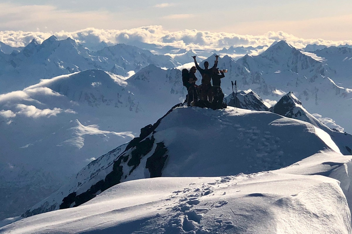 A group celebrate after reaching the top about to skiing down in the Turkey Zone, in the Chugach.